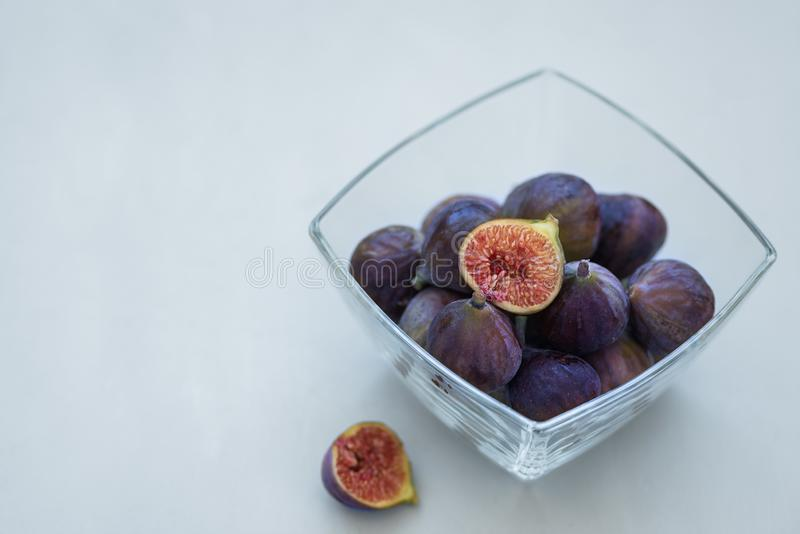 Fresh purple figs in glass bowl on gray wooden background. Soft focus. Harvesting time or healthy food concept.  royalty free stock photo