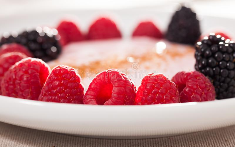 Raspberries and blackberries laid out on a white plate in circle with yogurt and cinnamon stock photography