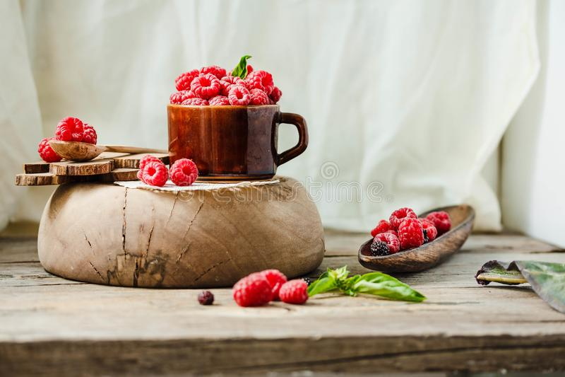 Fresh raspberry with basil in a cup of coffee and a wooden stand stock photography
