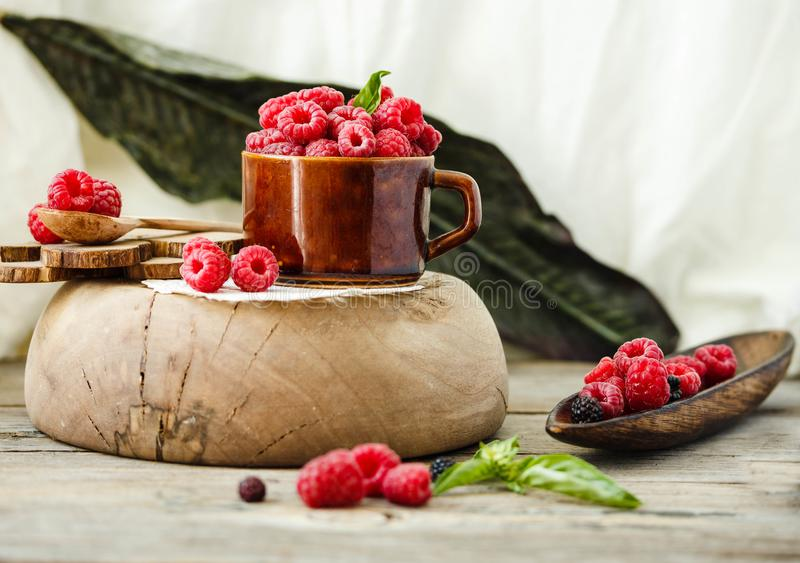 Fresh raspberry with basil in a cup of coffee and a wooden stand royalty free stock photo
