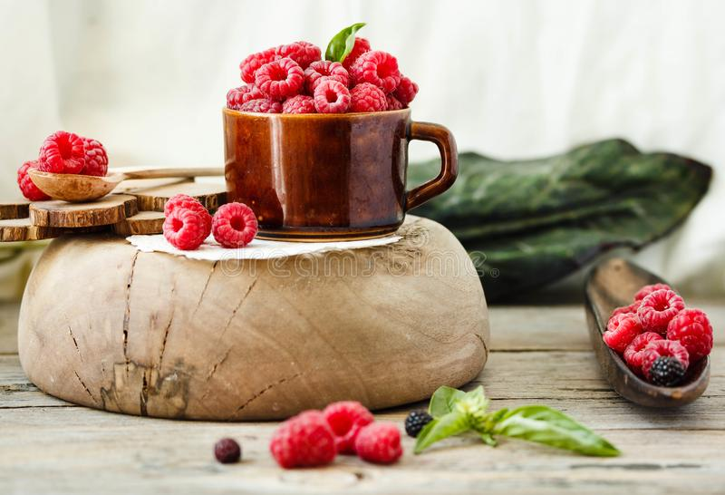 Fresh raspberry with basil in a cup of coffee and a wooden stand stock photos