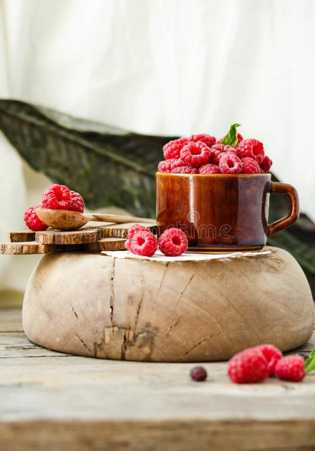 Fresh raspberry with basil in a cup of coffee and a wooden stand stock photo