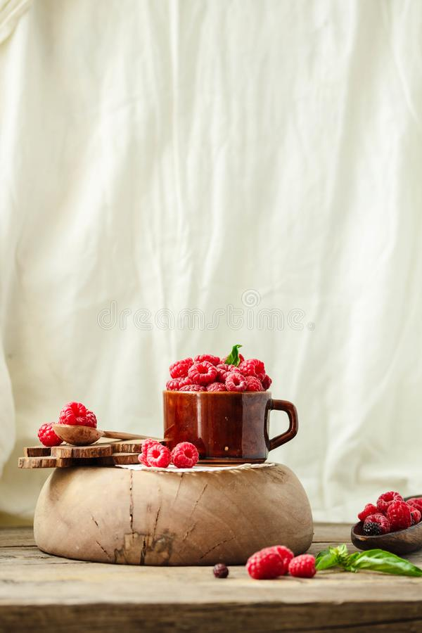 Fresh raspberry with basil in a cup of coffee and a wooden stand royalty free stock image