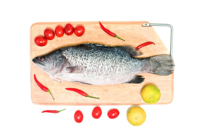 Fresh raw Asian Sea Bass fish on wooden cutting board with lemon, tomato and chilli on white background, top view. Seafood asian stock image