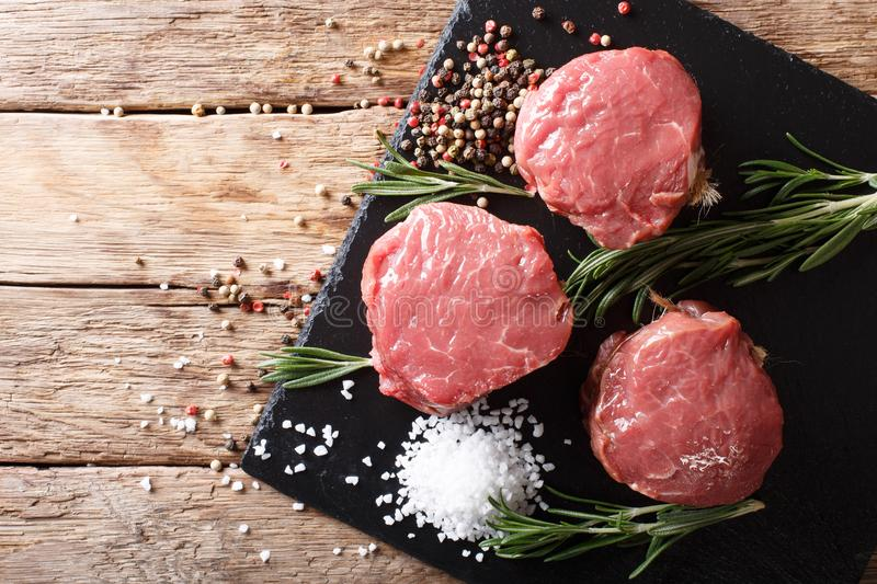 fresh raw beef fillet mignon on old wooden background. horizontal top view royalty free stock photography