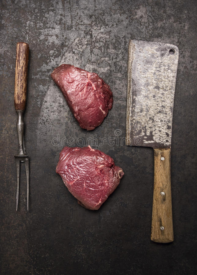 Fresh raw beef steak with meat cleaver on dark rustic background top view. Fresh raw beef steak meat cleaver on dark rustic background top view royalty free stock images