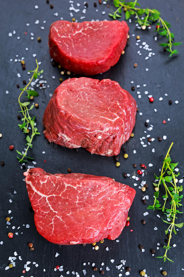 Fresh Raw Beef steak Mignon, with salt, peppercorns, thyme, garlic Ready to cook.  royalty free stock image