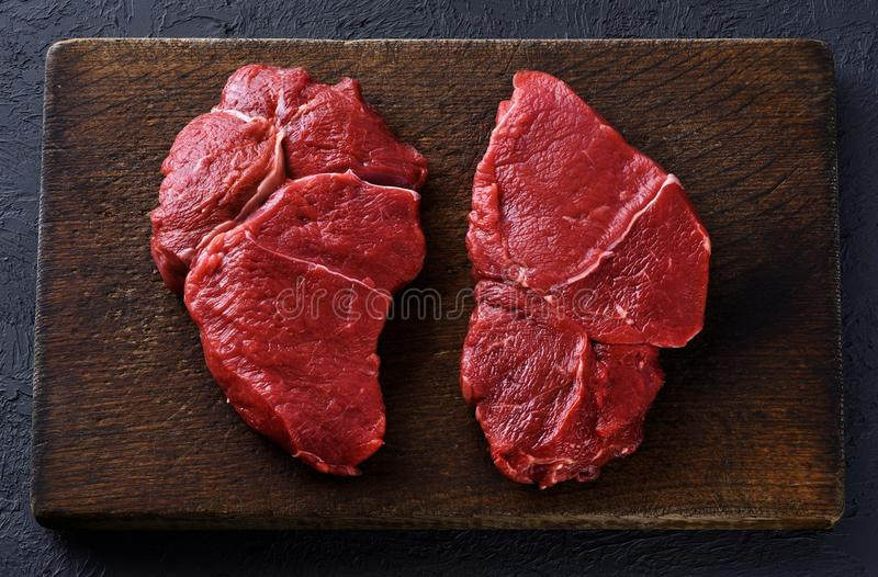 Fresh raw beef steaks on a dark wooden background. royalty free stock image
