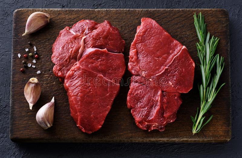 Fresh raw beef steaks, pepper, garlic, salt and rosemary stock photography