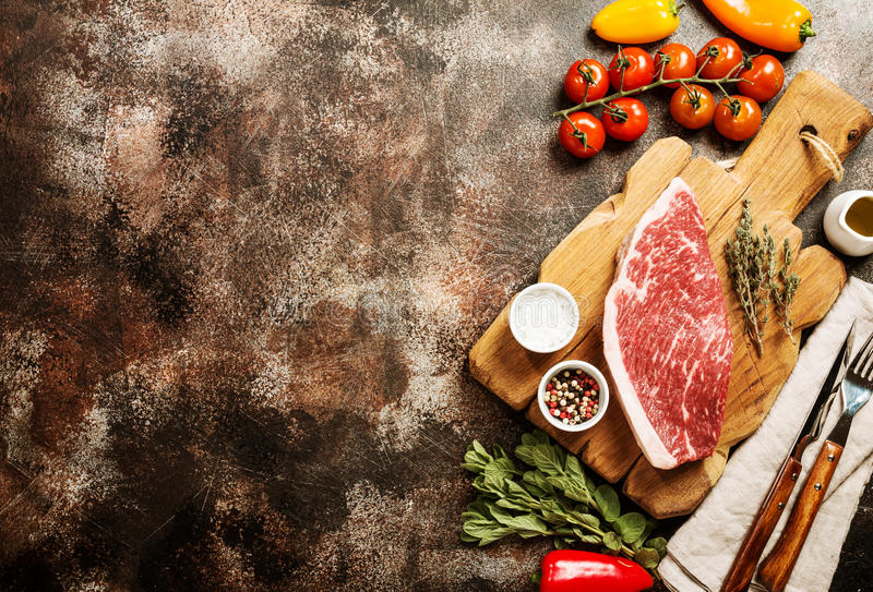 Fresh raw beef steaks. Fresh raw Prime Black Angus beef strip steaks on cutting board over dark rustic concrete background, top view. Ingredients set for making royalty free stock photography