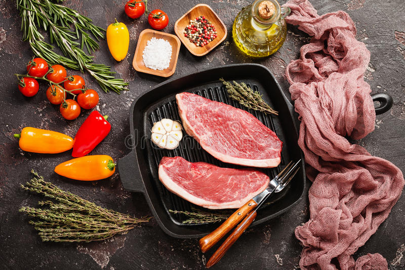 Fresh raw beef steaks. Fresh raw Prime Black Angus beef strip steaks on grill pan over dark rustic concrete background, top view. Ingredients set for making royalty free stock photo