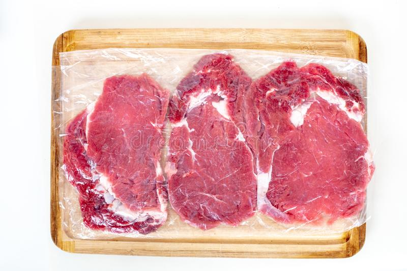 Fresh raw beef steaks in transparent vacuum packed. On wooden cutting board isolated on white background top view royalty free stock photos