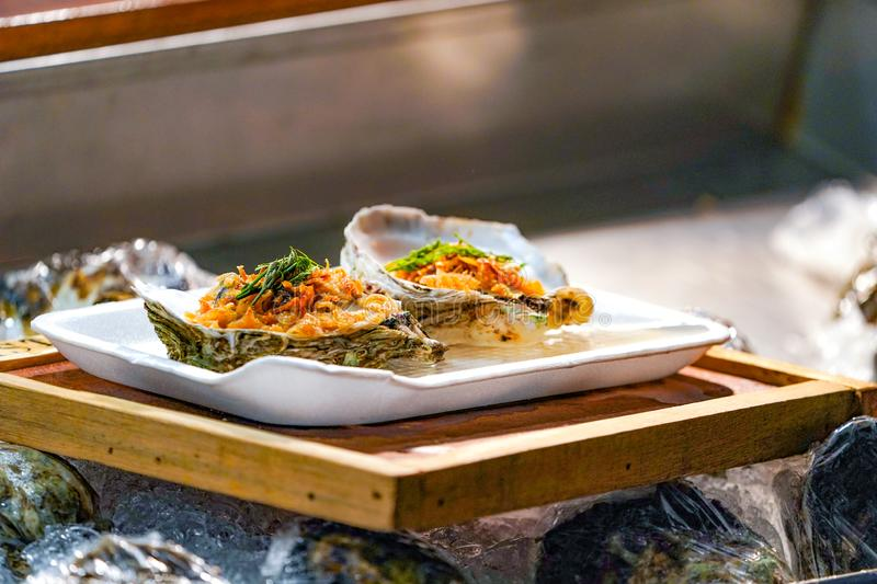 Fresh Raw big couple Oysters on the foam dish and wooden plate topping by fried garlic and leaf the ready to serve stock images