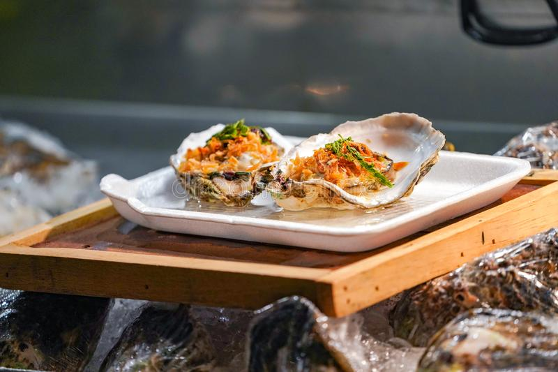 Fresh Raw big couple Oysters on the foam dish and wooden plate topping by fried garlic and leaf the ready to serve stock image