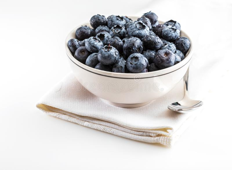 Fresh and raw blueberries in delicate white porcelain bowl. stock image