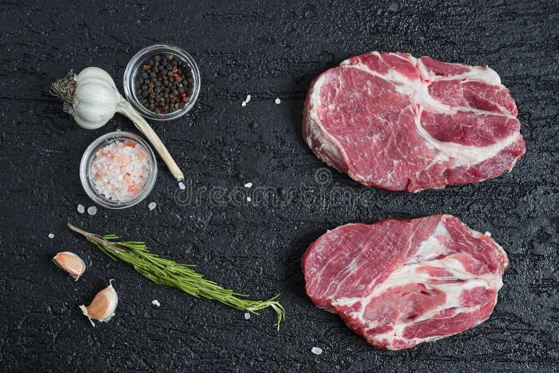 Fresh raw boneless pork neck slices on black stone background. royalty free stock photo