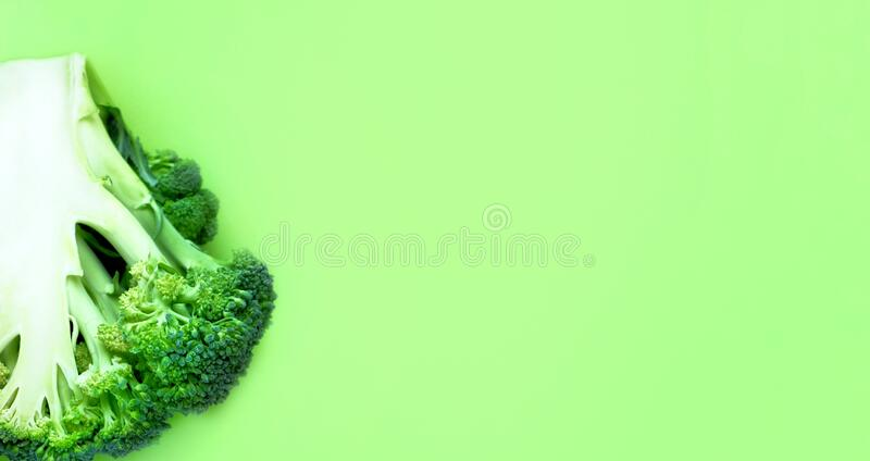 Fresh raw broccoli half on a green background. Abstract vegetable background, banner, cabbage texture details, close-up. Top view, flat lay with copy space for royalty free stock photography