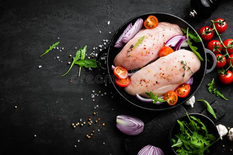 Fresh raw chicken meat, fillet marinated with spices, onion and tomatoes on black background. Top view royalty free stock photos