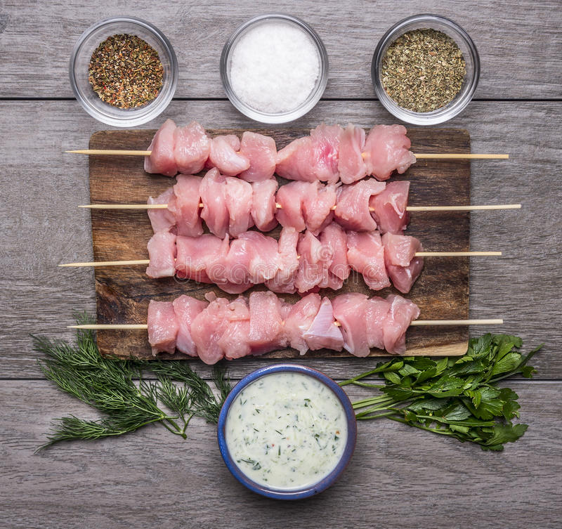 Fresh raw chicken pieces on skewers Seasoned Salt and garlic sauce greens on a cutting board royalty free stock photo