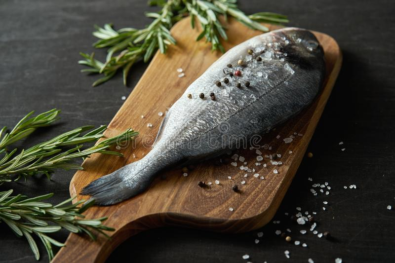 Fresh raw dorada fish with rosemary, pepper and salt on a wooden board and a black table royalty free stock photography