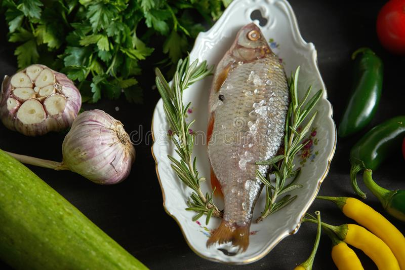 Fresh raw dorada fish in a white dish with a set of vegetables on a black table royalty free stock images