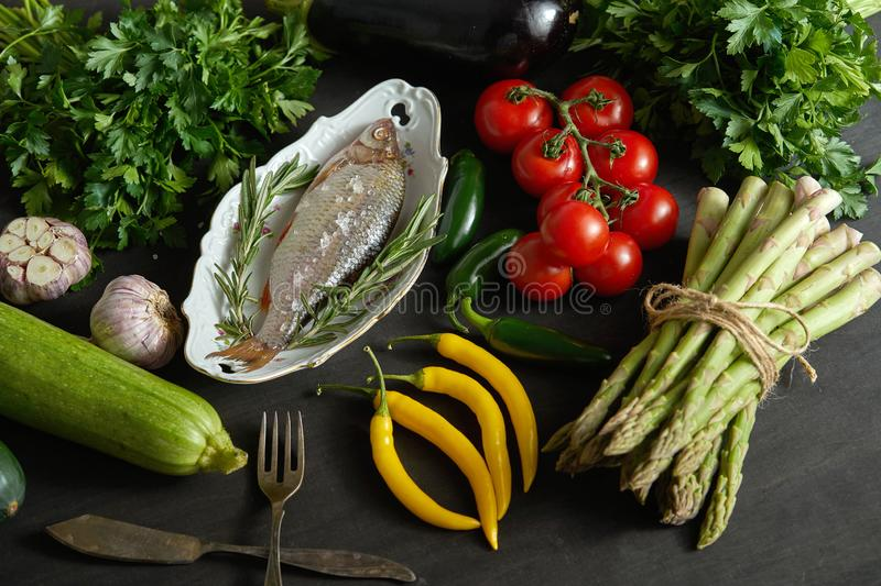 Fresh raw dorada fish in a white dish with a set of vegetables on a black table stock photography