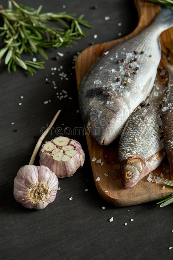 Fresh raw dorada fish on a wooden board with a sprig of rosemary and garlic on a black table. Three fresh raw dorada fish on a wooden board with a sprig of stock images