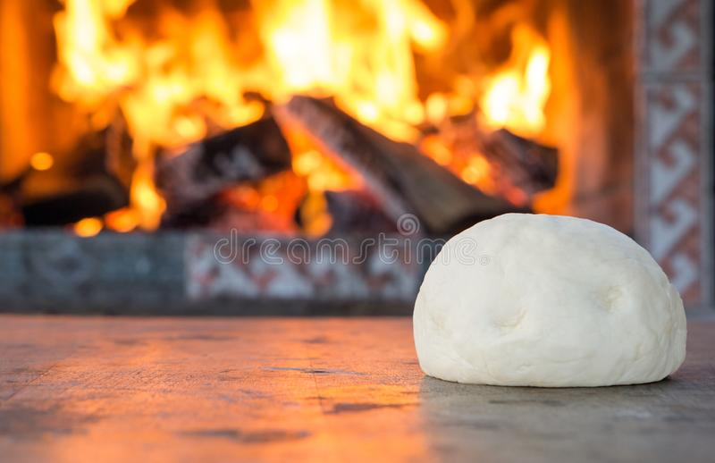 Fresh raw dough for pizza or bread baking on wooden table against the Burning fireplace. comfort mood concept royalty free stock images