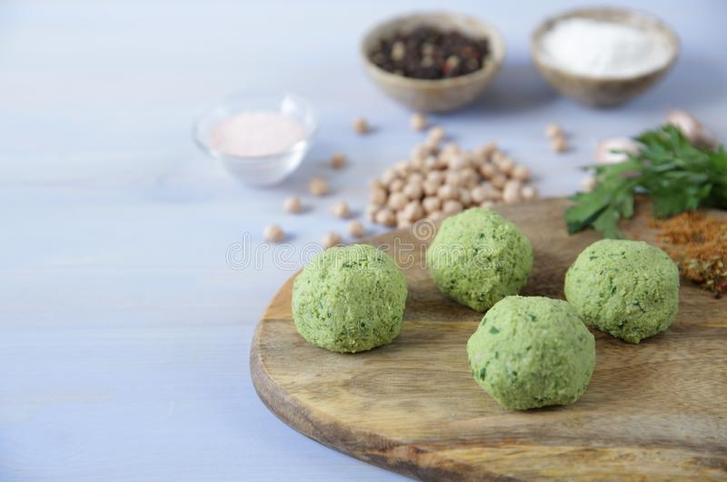 Fresh raw falafel balls of chickpeas, herbs and spices on a wooden cutting board on a light wooden background royalty free stock photo