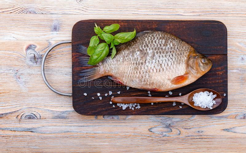 Fresh raw fish on a dark wooden background. Bream and spices. Green basil leaves, sea salt, wooden spoon.  royalty free stock photography