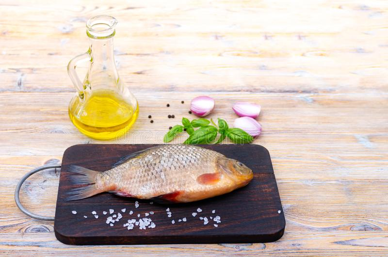 Fresh raw fish on a dark wooden background. Bream and spices. Green basil leaves, sea salt, wooden spoon.  royalty free stock photo