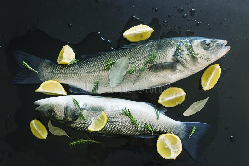 Fresh raw fish prepared for baking. Marinated in spices and stuffed with slices of juicy lemon and sprigs of rosemary. Dicentrarch. Us labrax. Concept- healthy stock photos