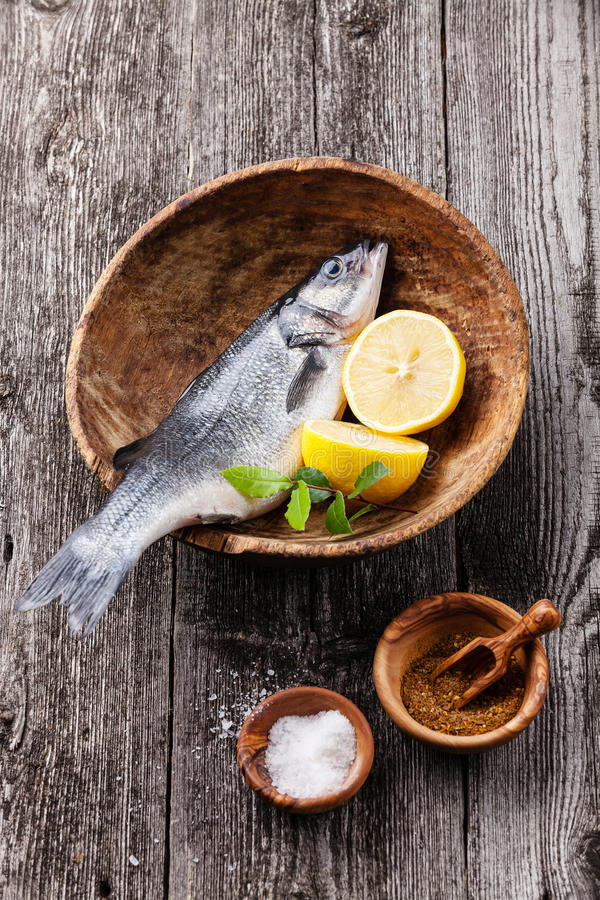 Fresh raw fish seabass. With salt, spices and lemon on textured wooden background stock photo