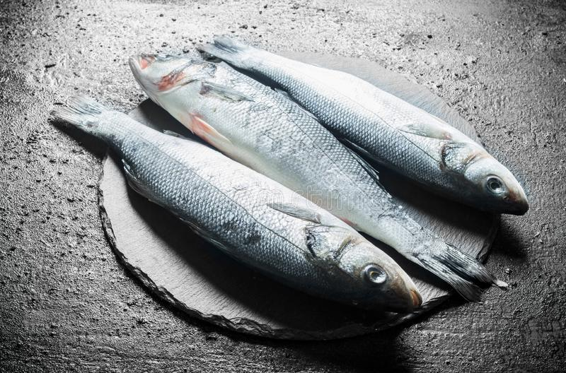 Fresh raw fish on a stone Board. On black rustic background royalty free stock photos