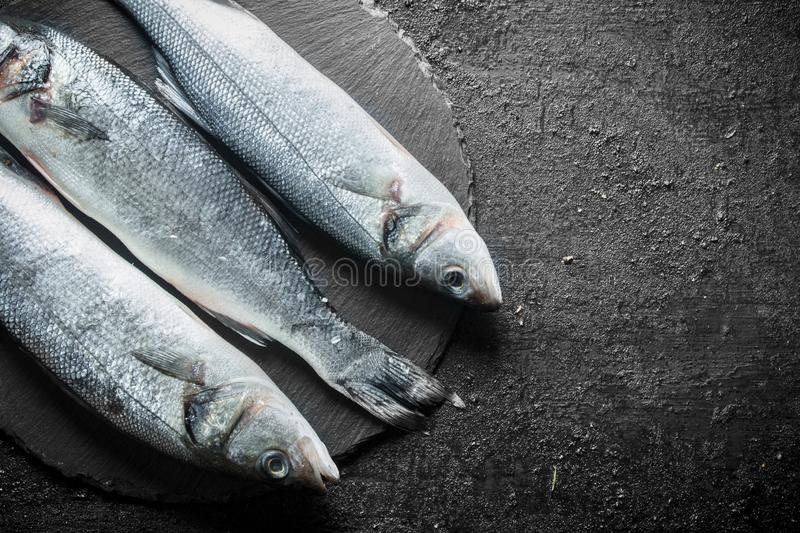 Fresh raw fish on a stone Board. On black rustic background stock photo