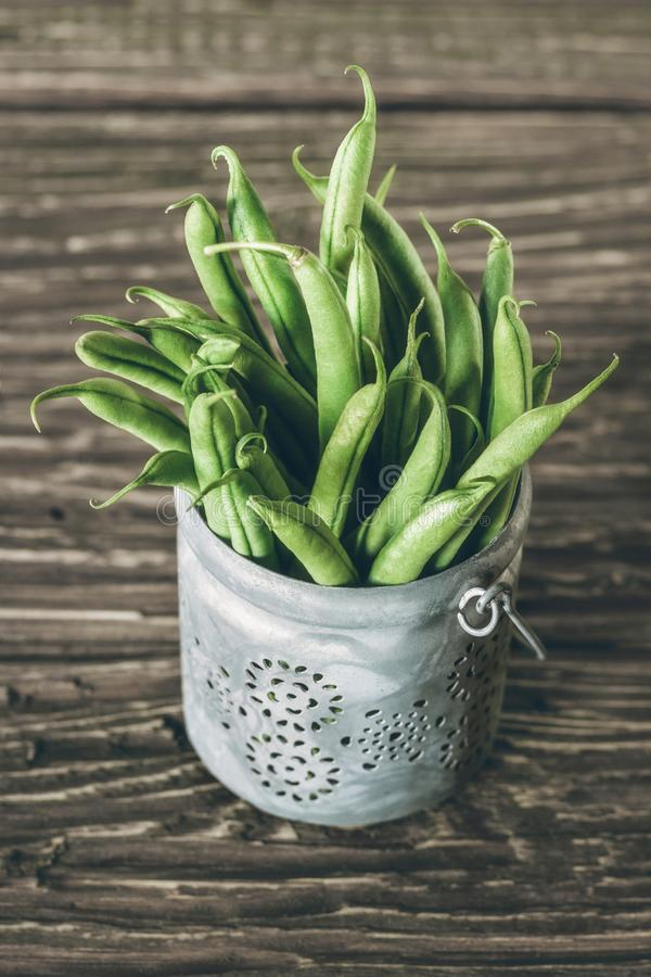 Fresh raw green beans in a bowl on wooden board stock image