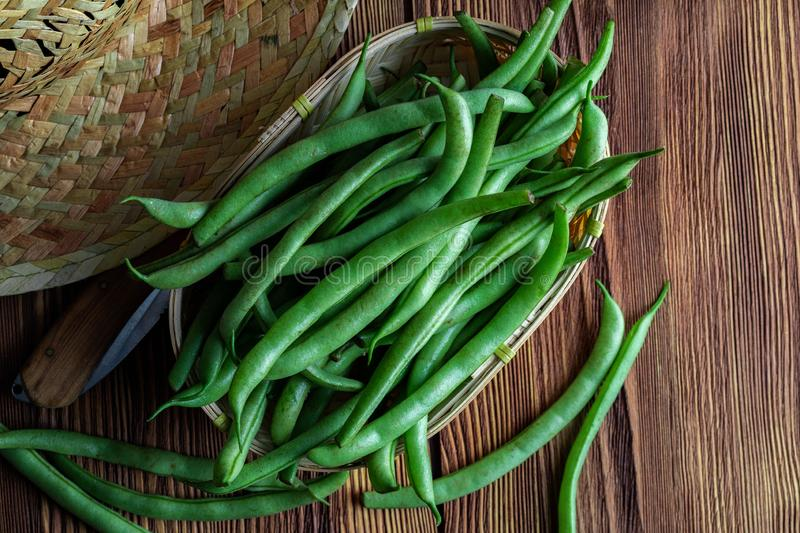 Fresh and raw green beans green round beans in wicker basket. Rustic and homemade look on wooden background. stock image