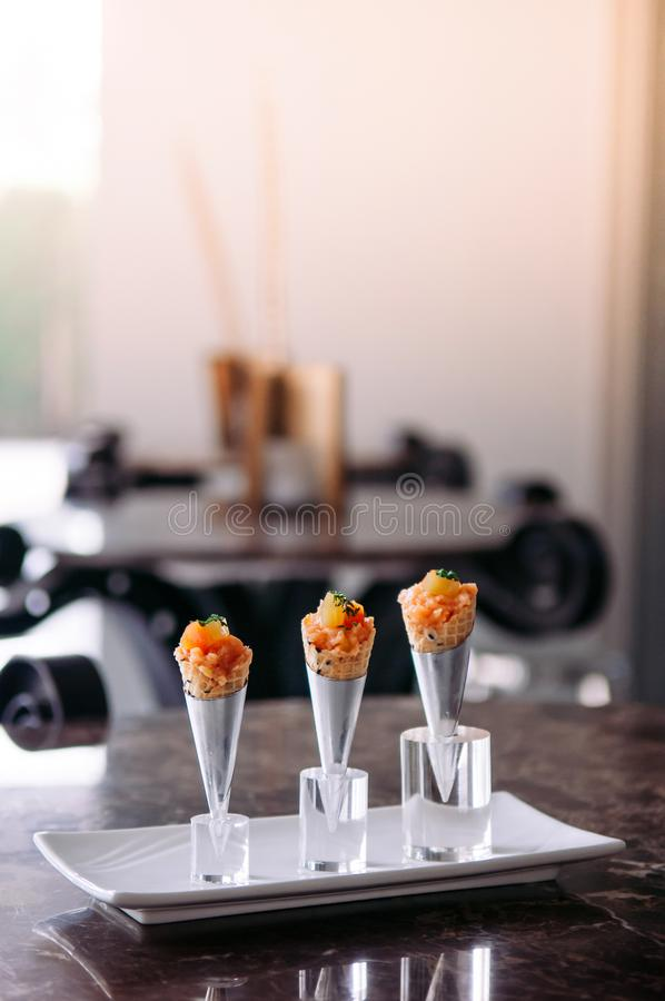 Fresh raw jouicy Salmon Tartare with tomato in mini waffle cones modern creative cuisine. Close up shot stock photos