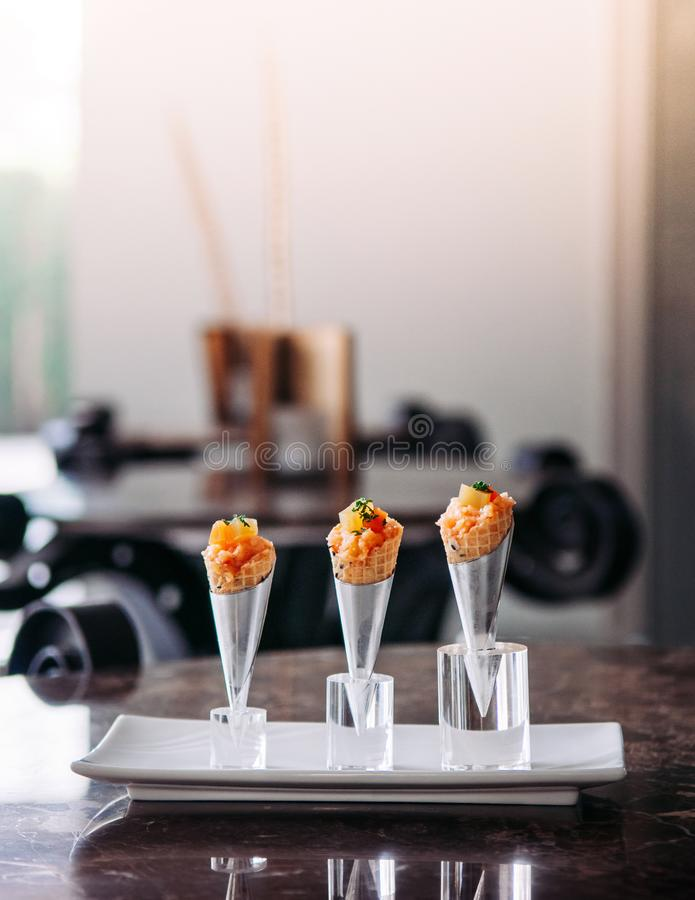 Fresh raw jouicy Salmon Tartare with tomato in mini waffle cones modern creative cuisine. Close up shot stock photo