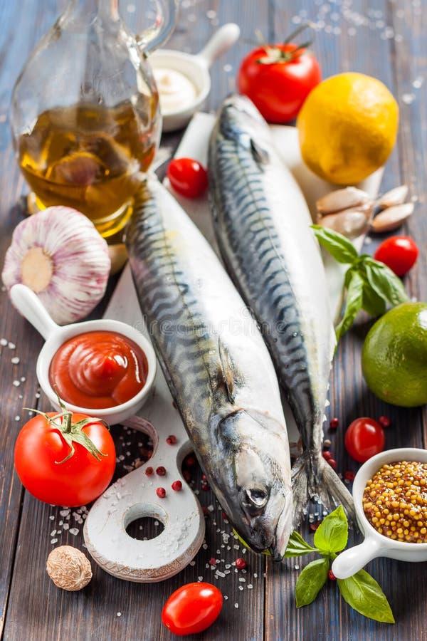 Fresh raw mackerel with lemon, tomatoes and spices on parchment. Preparing to bake. Fresh raw mackerel with lemon, garlic and tomatoes, prepared for roasting stock photos