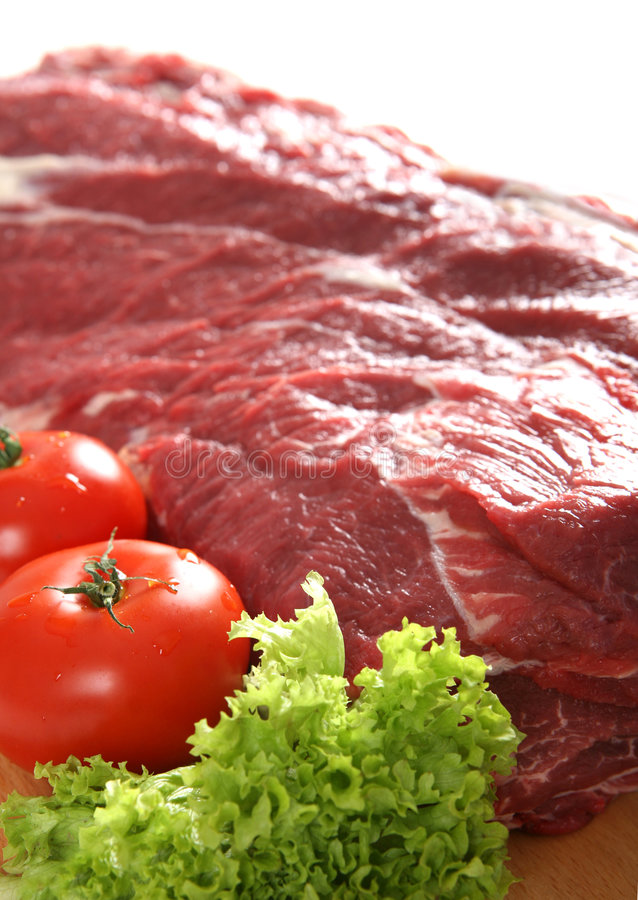 Fresh raw meat. With tomatoes and lettuce stock photo