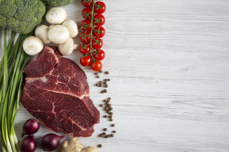 Fresh raw meat beef steak with spices, cherry tomatoes, health f royalty free stock photography