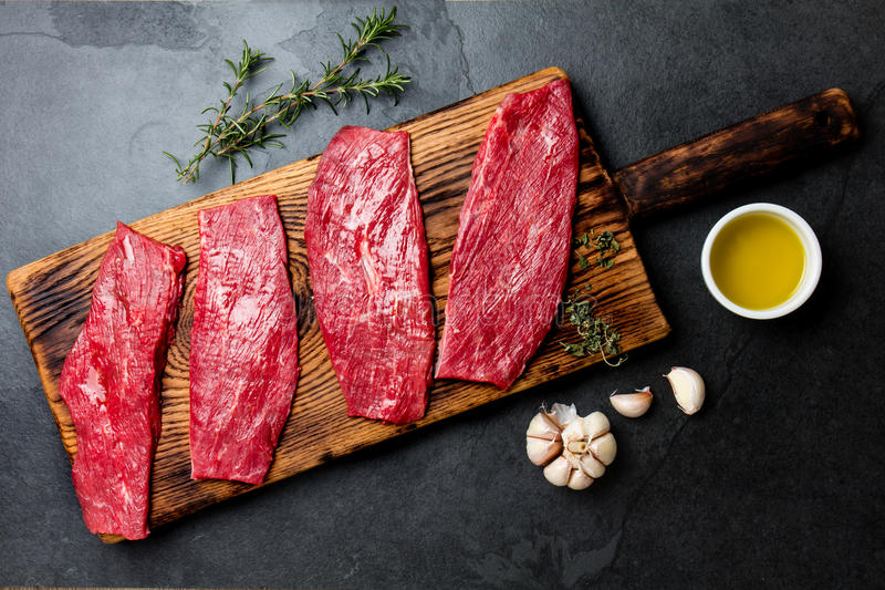 Fresh raw meat beef steaks. Beef tenderloin on wooden board, spices, herbs, oil on slate gray background. Food cooking background stock photo