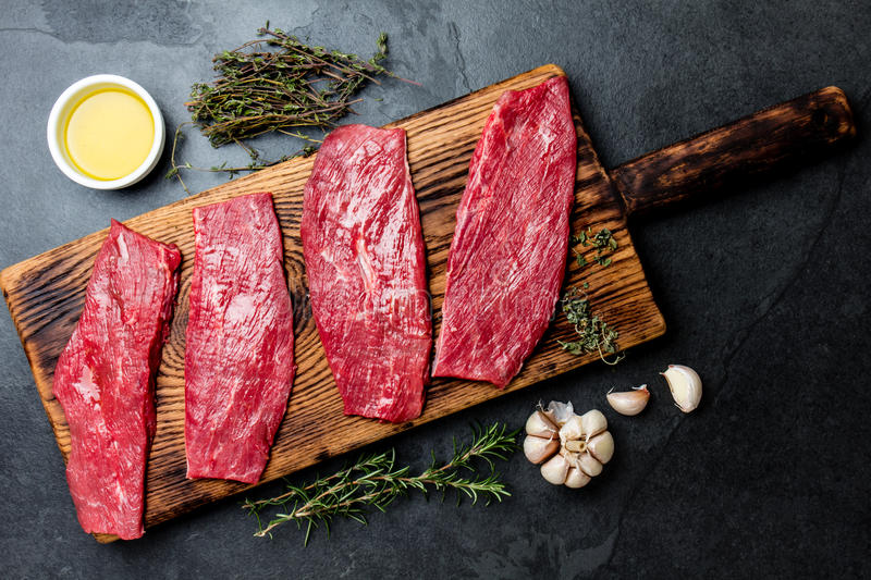 Fresh raw meat beef steaks. Beef tenderloin on wooden board, spices, herbs, oil on slate gray background. Food cooking background royalty free stock photos