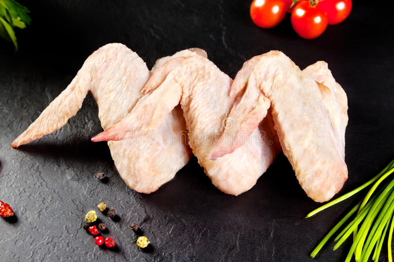 Fresh and raw meat. Chicken wings white ready to cook. Background black blackboard stock photography