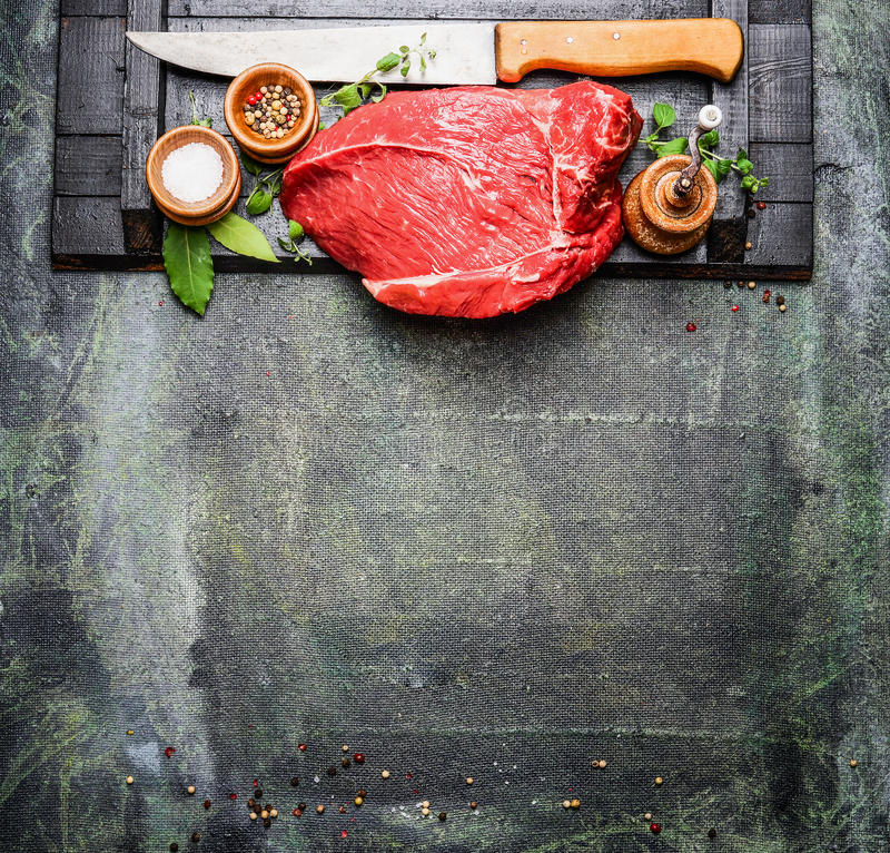 Fresh raw meat with cooking seasoning and butcher knife on rustic background. Top view royalty free stock photos