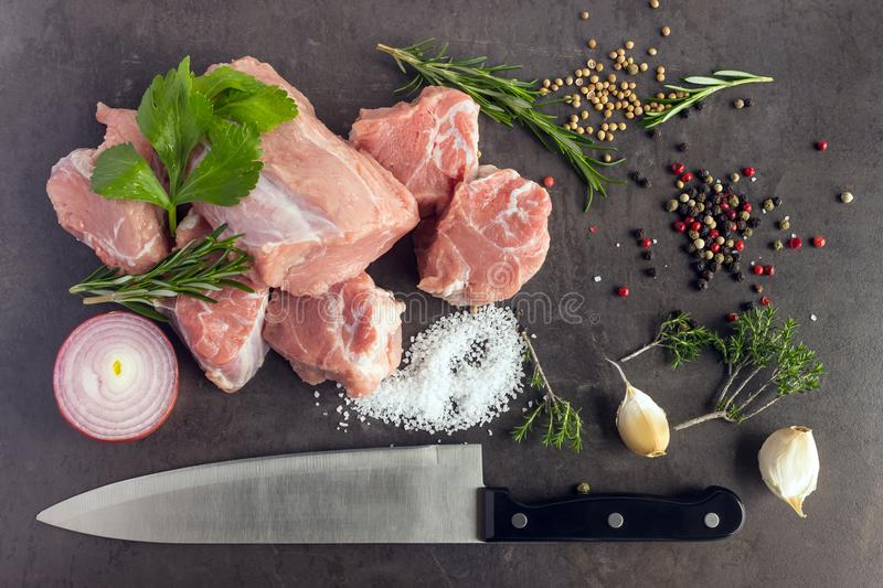 Fresh raw meat with herbs, spices and a butcher knife lies on th. E surface of a dark stone. Cooking concept royalty free stock images