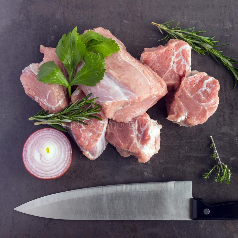 Fresh raw meat with herbs, spices and a butcher knife lies on th. E surface of a dark stone. Cooking concept royalty free stock photos