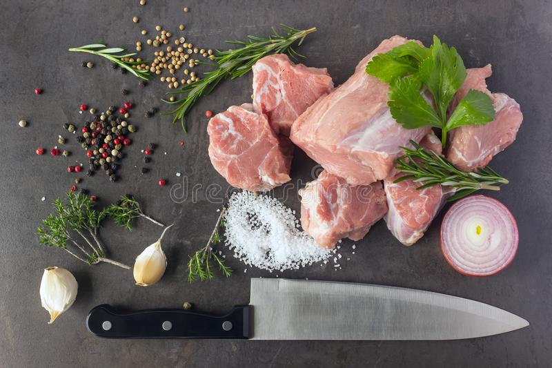 Fresh raw meat with herbs, spices and a butcher knife lies on th. E surface of a dark stone. Cooking concept royalty free stock photo