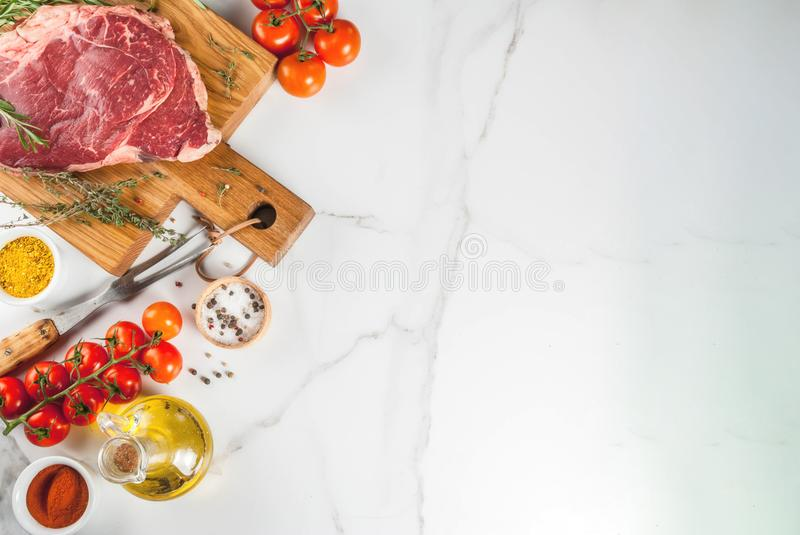 Fresh raw meat, lamb or beef steak. Fresh raw meat, lamb beef marble steak on a cutting board, with ingredients for cooking. On white marble table, copy space royalty free stock image